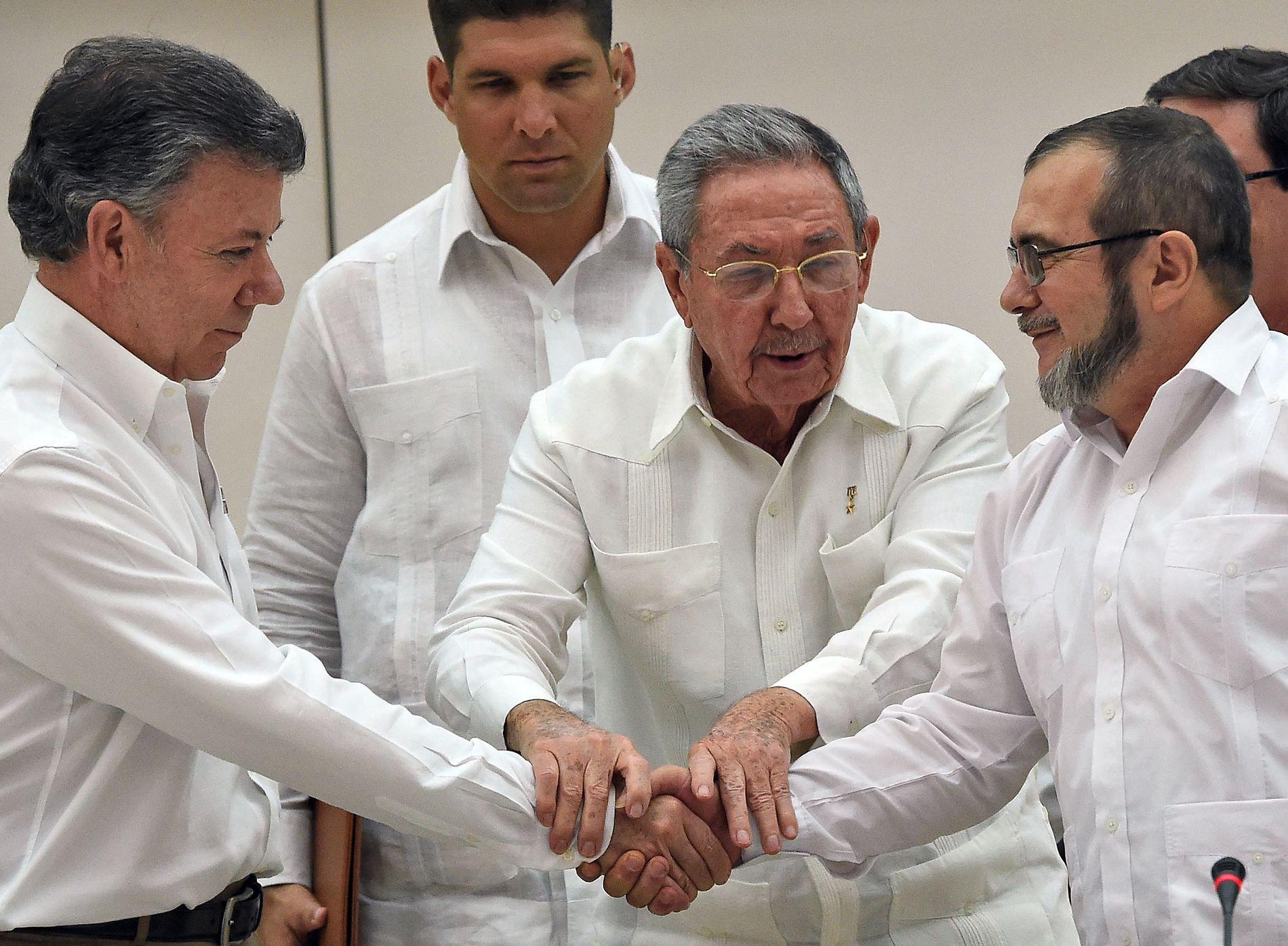 HISTORISK HÅNDTRYKK: Dette er scener som ville vært helt utenkelige for bare få år siden. Colombias president Juan Manuel Santos (til venstre) i et hjertelig håndtrykk med FARC-toppen Timoleon «Timochenko» Jimenez - mens de får en håndsrekning av Cubas president Raul Castro (i midten).