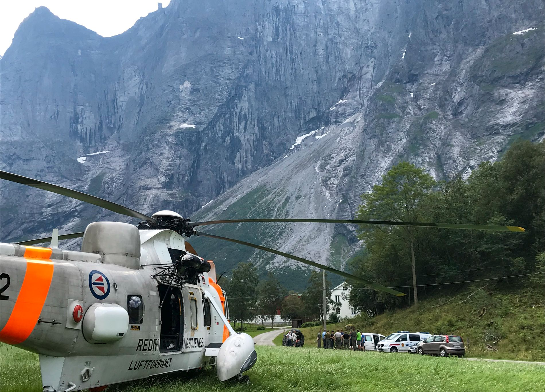 ADJUSTMENT: Rescue helicopters, police and investigative crews are on the floor of the valley below the Troll Wall in July.