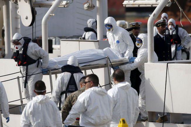 KATASTROFE: Den italienske kystvakten bar mandag morgen i land omkomne etter lørdagens forlis. Myndighetene frykter at det kan ha vært opptil 950 personer på båten.