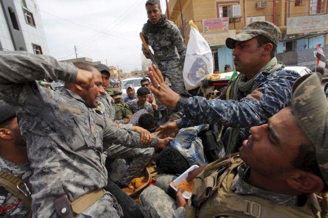 AGGRESIVT: Et medlem av irakiske sikkerhetsstyrker banker en person mistenkt for å tilhøre IS i Tikrit i april.