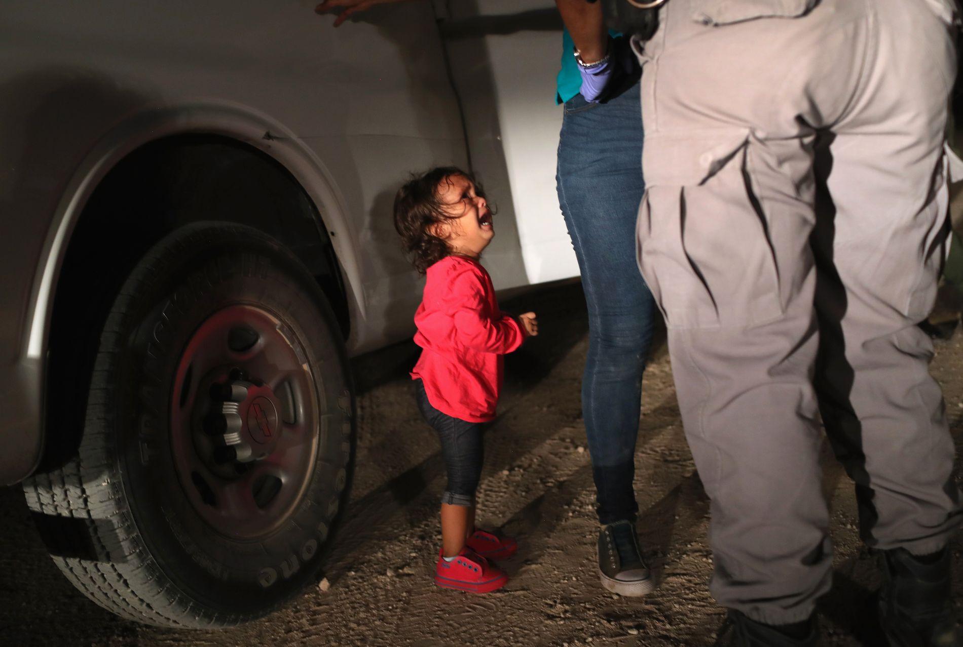 GRÅTER: Dette bildet skal vise en to år gammel jente fra Honduras. Hun bryter ut i gråt idet hennes mor blir ransaket og arrestert ved grensen mellom USA og Mexico 12. juni i år, ifølge bildebyrået Getty. De skriver at asylsøkerne hadde tatt seg over Rio Grande før de ble pågrepet og sendt videre til et senter. Det vites ikke om jenta ble skilt fra moren.