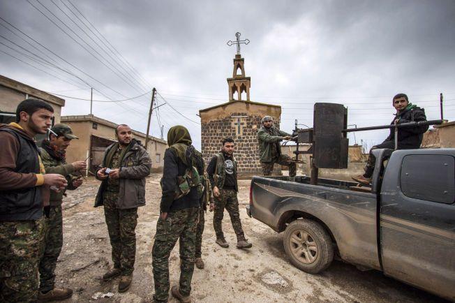 Kurdiske soldater står foran en kirke i den assyriske landsbyen Tel Jumaa, nord for Tel Tamr 25. februar. De assyriske kristne skal ha blitt bortført fra landsbyer nær Tel Tamr, cirka 20 kilometer nordvest for Hasaka. Ingen vet hvordan de har det.