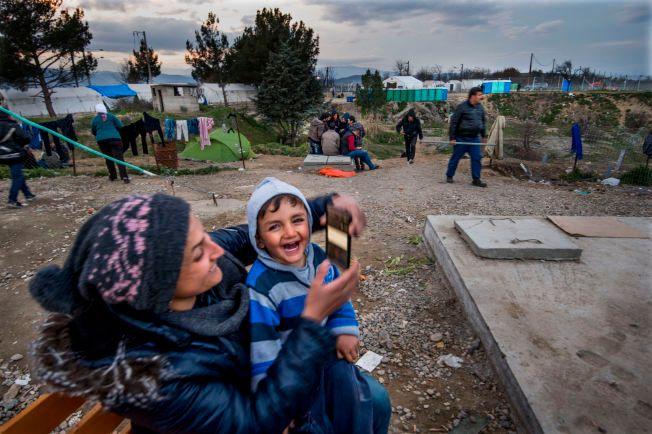 I GRENSELAND: Fra benken i flyktningleiren Idomeni nord i Hellas, holder Karim (2,5) og mamma kontakt med faren i Tyskland via Skype. Hvor lenge de må vente før de får krysse grensen i bakgrunnen og reise nordover, aner de ikke.