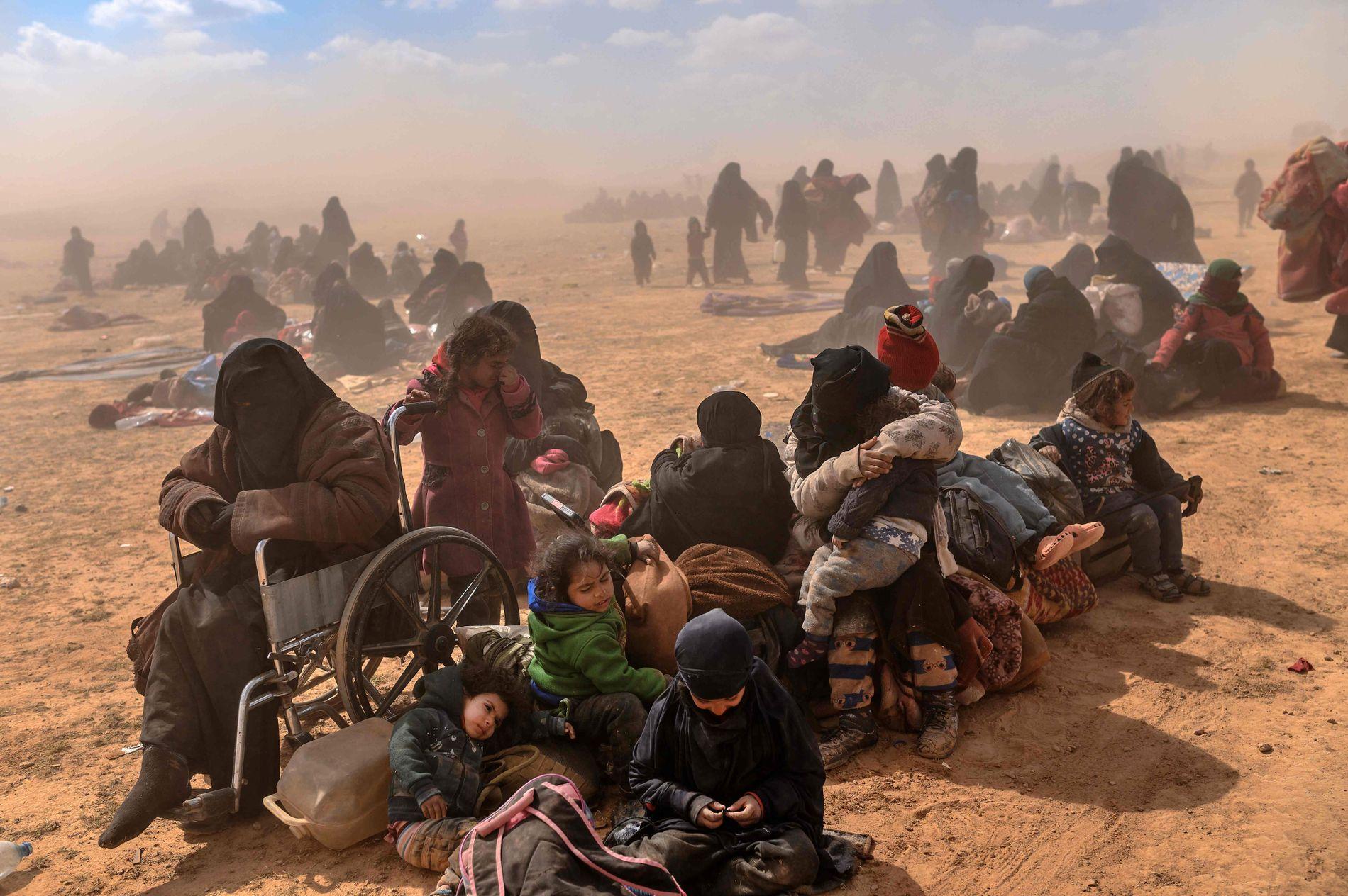 DESPERATE: En familie sitter på bakken etter å ha forlatt IS-området, og venter på å bli sikkerhetskontrollert av SDF.