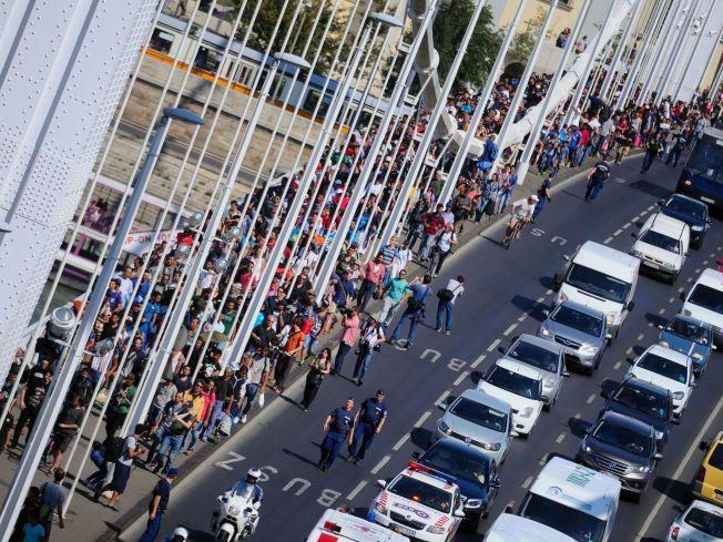 VIL GÅ TIL GRENSEN: Hundrevis av flyktninger går på Elisabet-broen etter å ha forlatt transitsonen på Budapest sentralbanestasjon fredag, med planer om å gå til den østerrikske grensen.