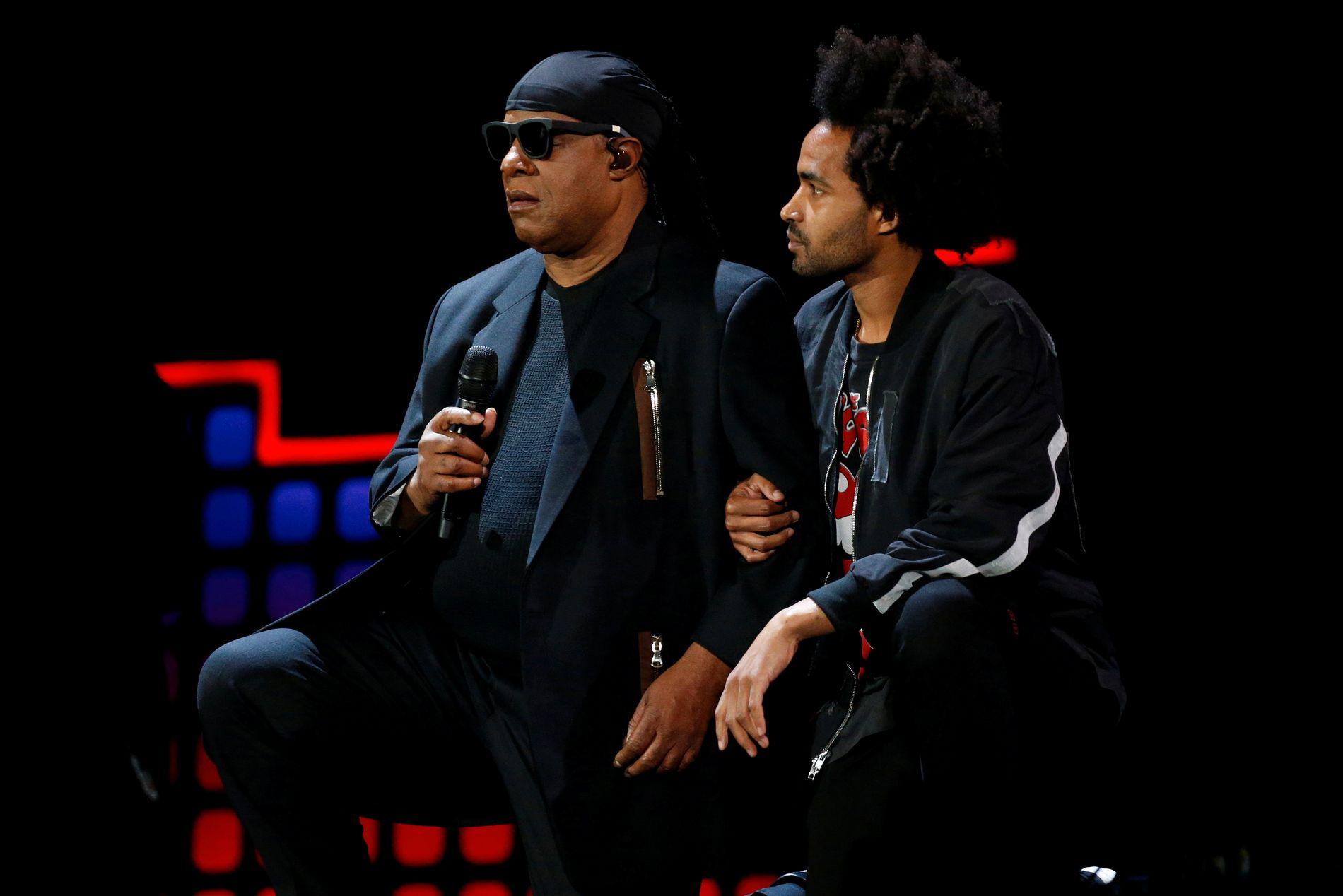 KNELTE: Stevie Wonder og sønnen Kwame kneler på Global Citizens Festival i Central Park lørdag.