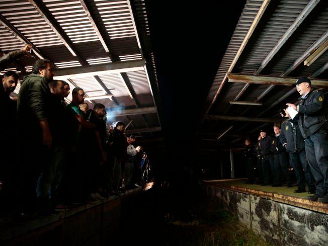 ANSPENT: Ved 21-tiden onsdag kveld var stemningen anspent ved togene i Rødby. Flyktning-støttespillerne flyttet seg nærmere togene mens de ropte taktfast, men ble presset bakover igjen av politiet.