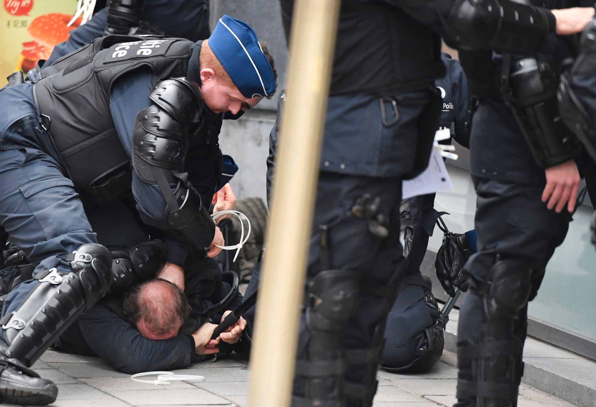 Belgisk politi pågriper demonstranter ved EU-kvartalet i Brussel lørdag. Foto: AP / NTB scanpix.