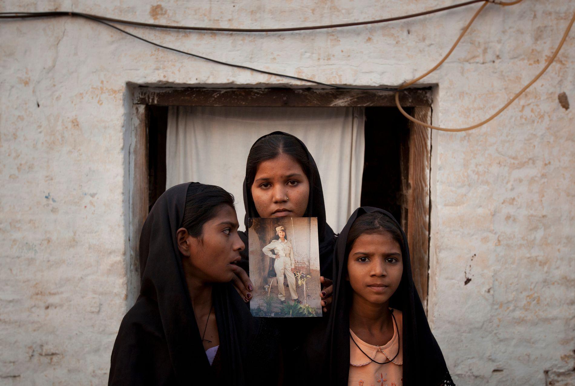 DØTRENE: Asia Bibis døtre holder opp et bilde av moren utenfor sitt hjem i Sheikhupura i Punjab-provinsen i 2010, året da Bibi ble dømt til døden. I dag bor de i Canada.