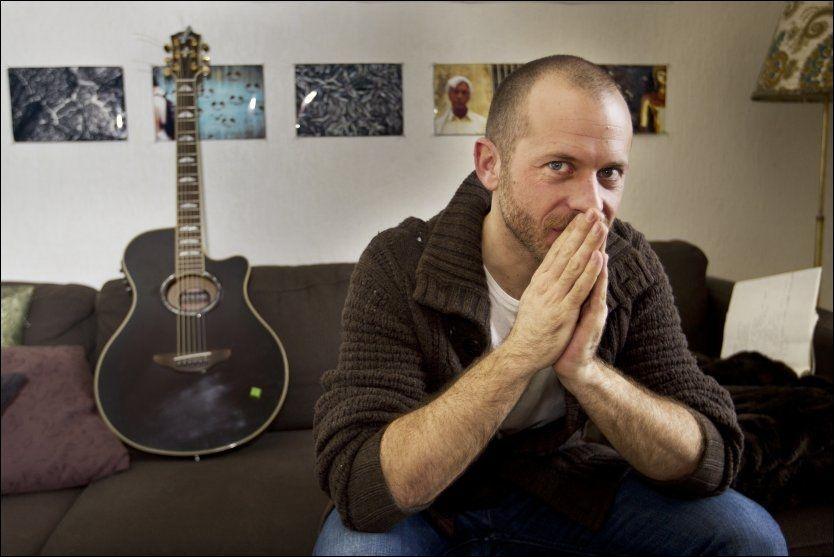 HJEMME I SOFAEN: Shaun Bartlett har gitarer overalt hjemme leilgheten på Grünerløkka. Og på veggene har han bilder han selv har tatt på reiser. Foto: Roger Neumann.