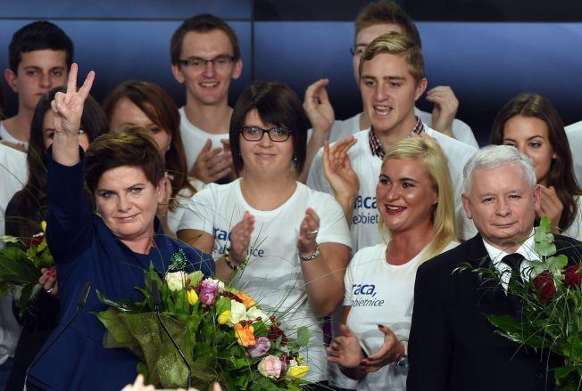 BRAKVALG: Partileder Jaroslaw Kaczynski (til høyre) og statsministerkandidat Beata Szydlo feiret med partimedlemmer på partikontoret etter at valgdagsmålingene viste rent flertall til partiet søndag kveld.