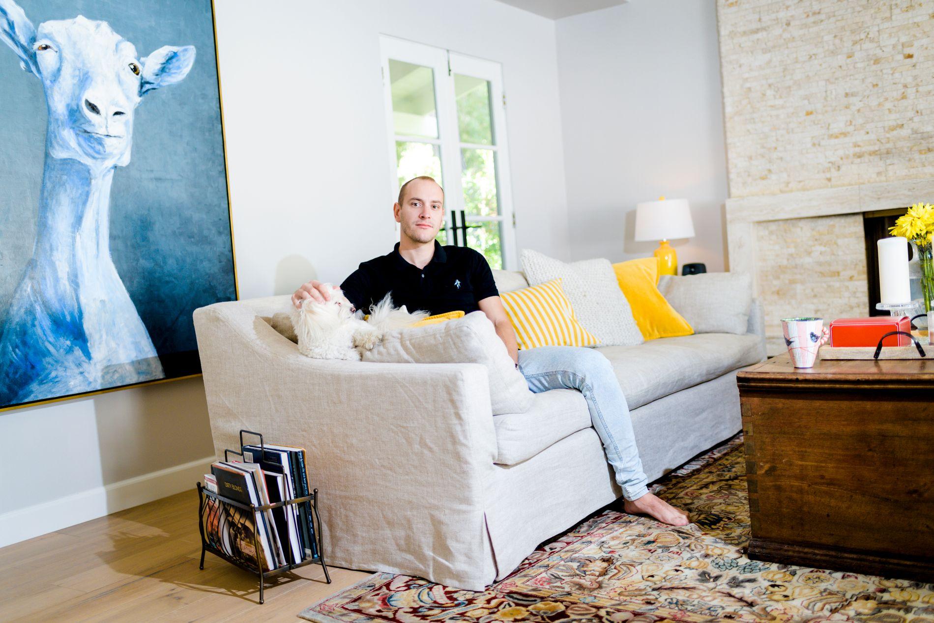 SUKSESS: Musikkprodusent og låtskriver Andreas Schuller har bodd i LA i syv år og mener det viktigste for å slå gjennom i USA er å faktisk bo der. Her sitter han i stuen sin foran ett bilde av en geit han har malt selv med hunden Nala ved siden av seg.