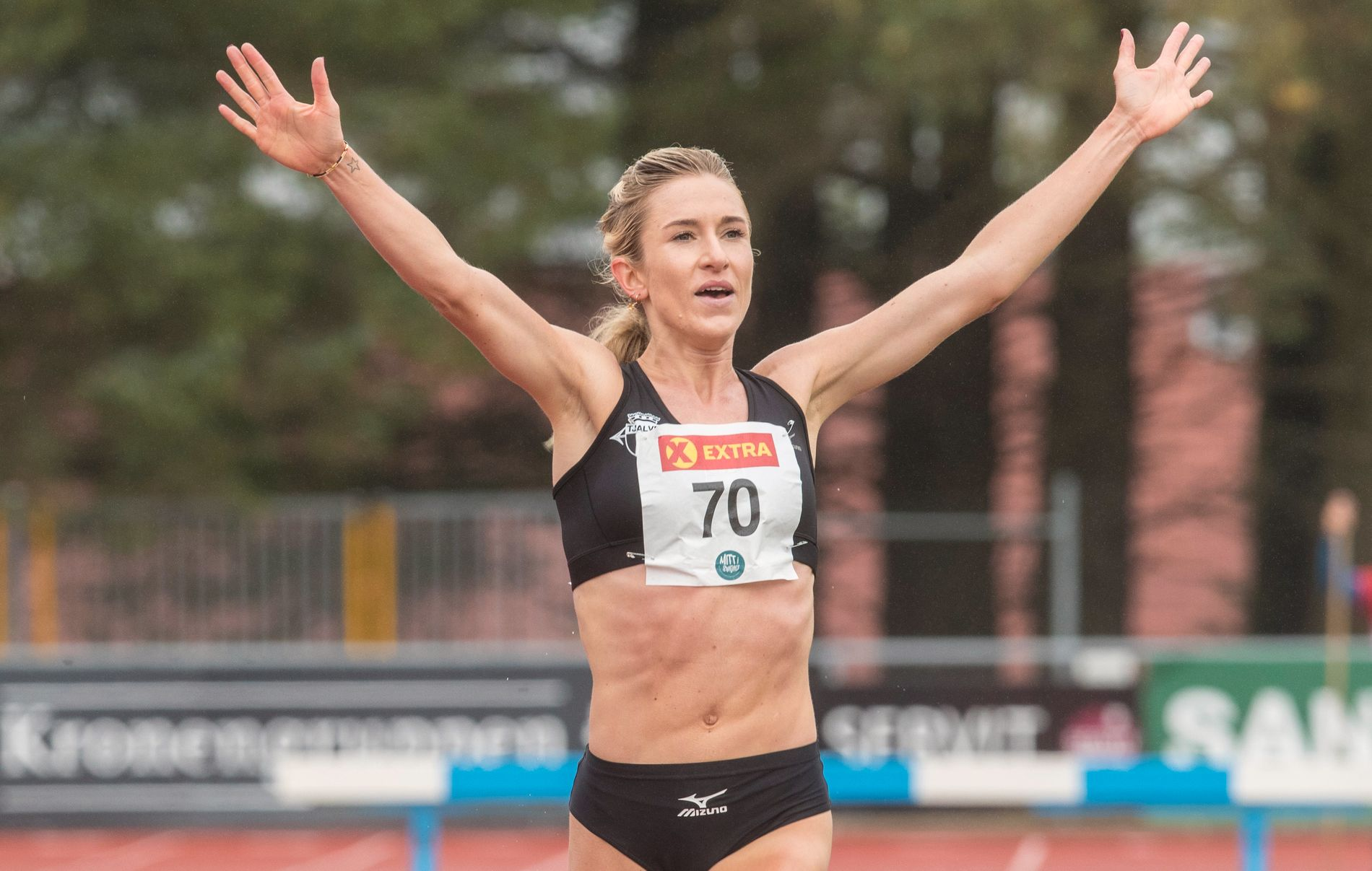 NM-GULL: Karoline Bjerkeli Grøvdal strekker armene i været idet hun passerer mållinjen etter gulløpet på 3000 meter hinder i Sandnes den 26. august i år.