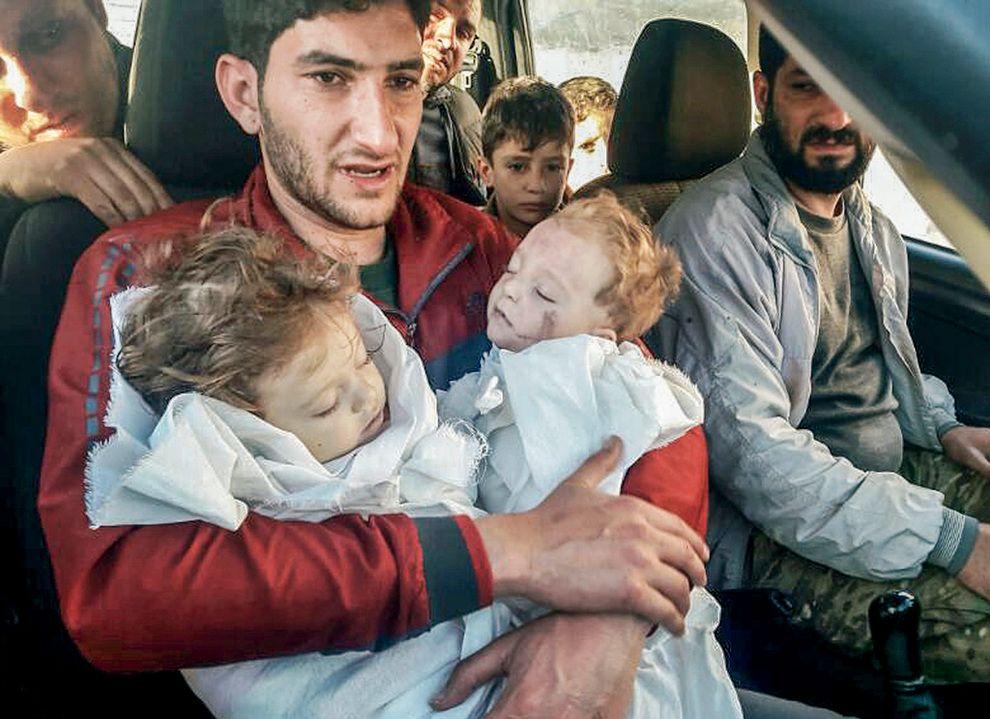 FARVEL: Abdel-Hameed Alyousef ba en slektning om å ta bilde av hans farvel med sine to barn, som døde i det kjemiske angrepet i Syria i april. Her er han på vei for å begrave dem i en massegrav.