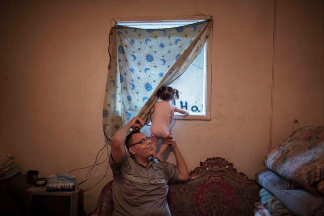 DYSTER UTSIKT: Ettåringen titter nysgjerrig ut mot flyktningleiren fra farens skuldre. Forholdene her beskrives av FN som «ekstremt dårlige».