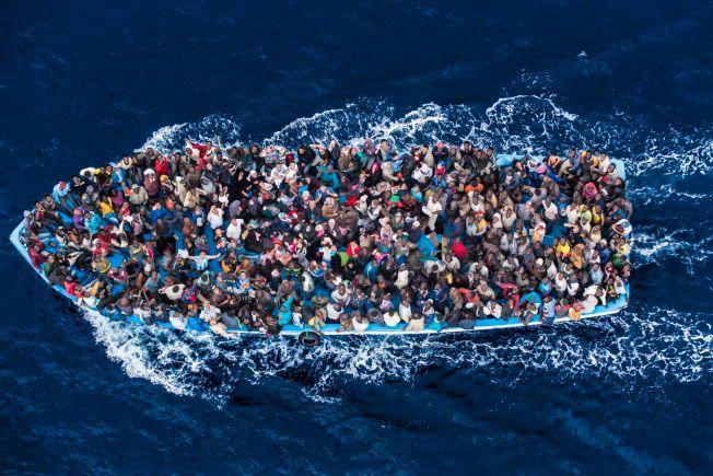 OVERFYLT: En flyktningbåt blir plukket opp av den italienske kystvakten. Bildet er tatt 7. juni 2014.