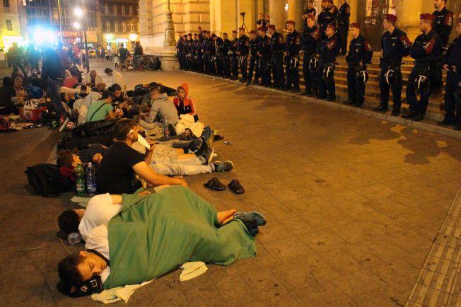 JERNRING: For andre natten på rad holder politiet natt til onsdag vakt rundt togstasjonen i Budapest mens flyktninger sover utenfor.
