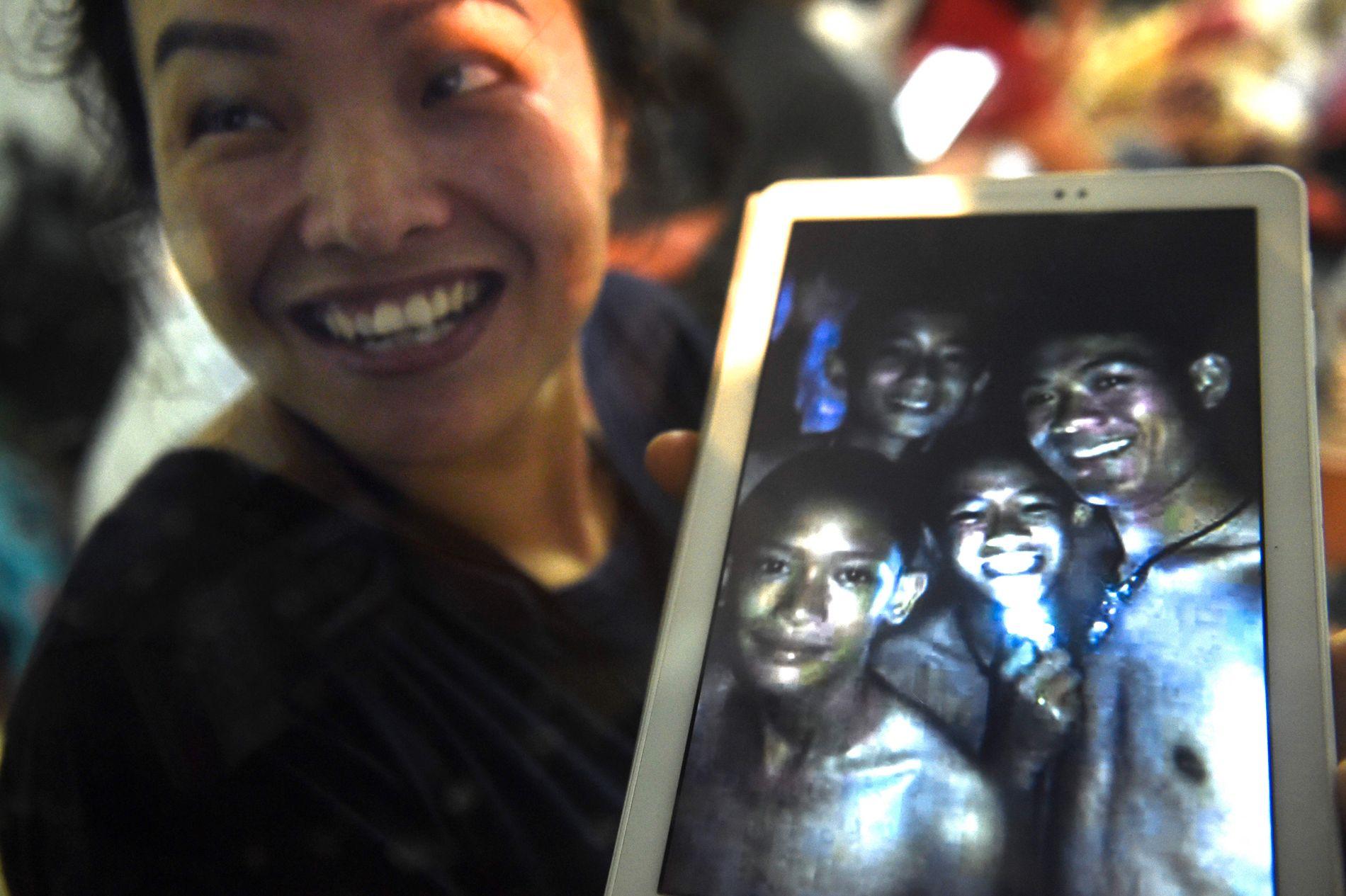 MOR: Thanaporn Promthep, moren til en av de 12 savnede guttene, viser frem et bilde av sønnen Duangpetch Promthep, som også har kallenavnet «Dom» avbildet som nummer to til høyre med det skarpe lyset. Fotballtrener Ekkapol Chantawong til høyre. De to andre guttene (til venstre) er ikke fanget i grotten.