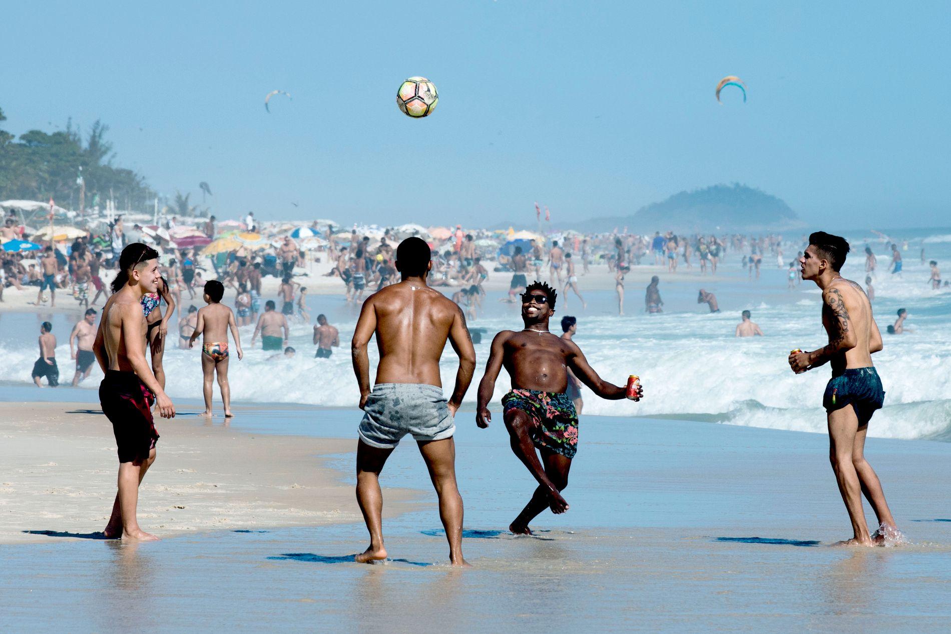 MØRKT BAK IDYLLEN: Det er ingenting å si på humøret til denne gjengen som spiller fotball på stranden i voldsherjede Rio de Janeiro. 1127 personer ble drept av politiet eller militære styrker i Rio i 2017, en økning på 19 prosent fra året før. 119 politifolk ble drept.