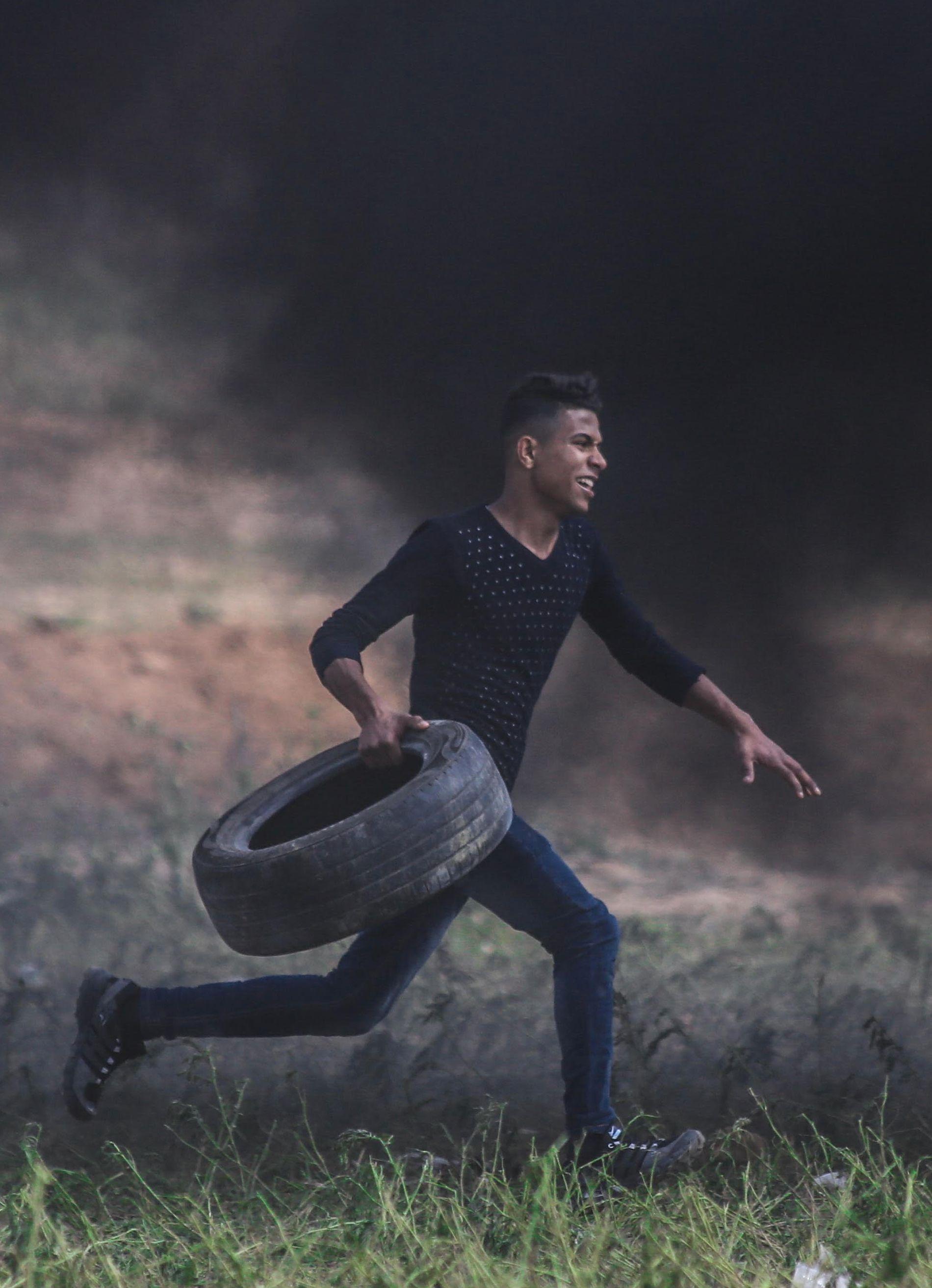 DET SISTE BILDET: Abdul Fattah Abdul Nabi løper med et bildekk i hendene rett før han blir skutt og drept.