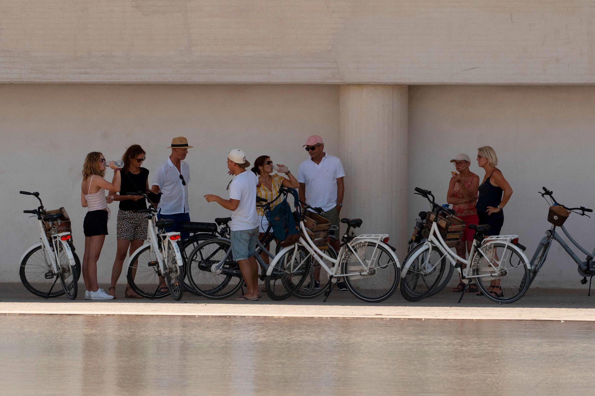 Turister i den spanske byen Valencia står i skyggen med syklene sine. Bildet er tatt under den første hetebølgen tidligere i sommer.