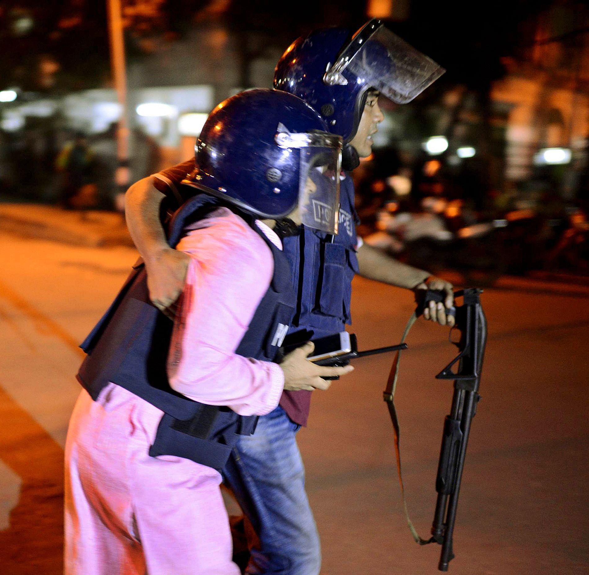 SIKKERHET: En uidentifisert person blir brakt i sikkerhet nær kafeen hvor 20 personer, deriblant flere utlendinger, blir holdt som gisler i Dhaka, Bangladesh.