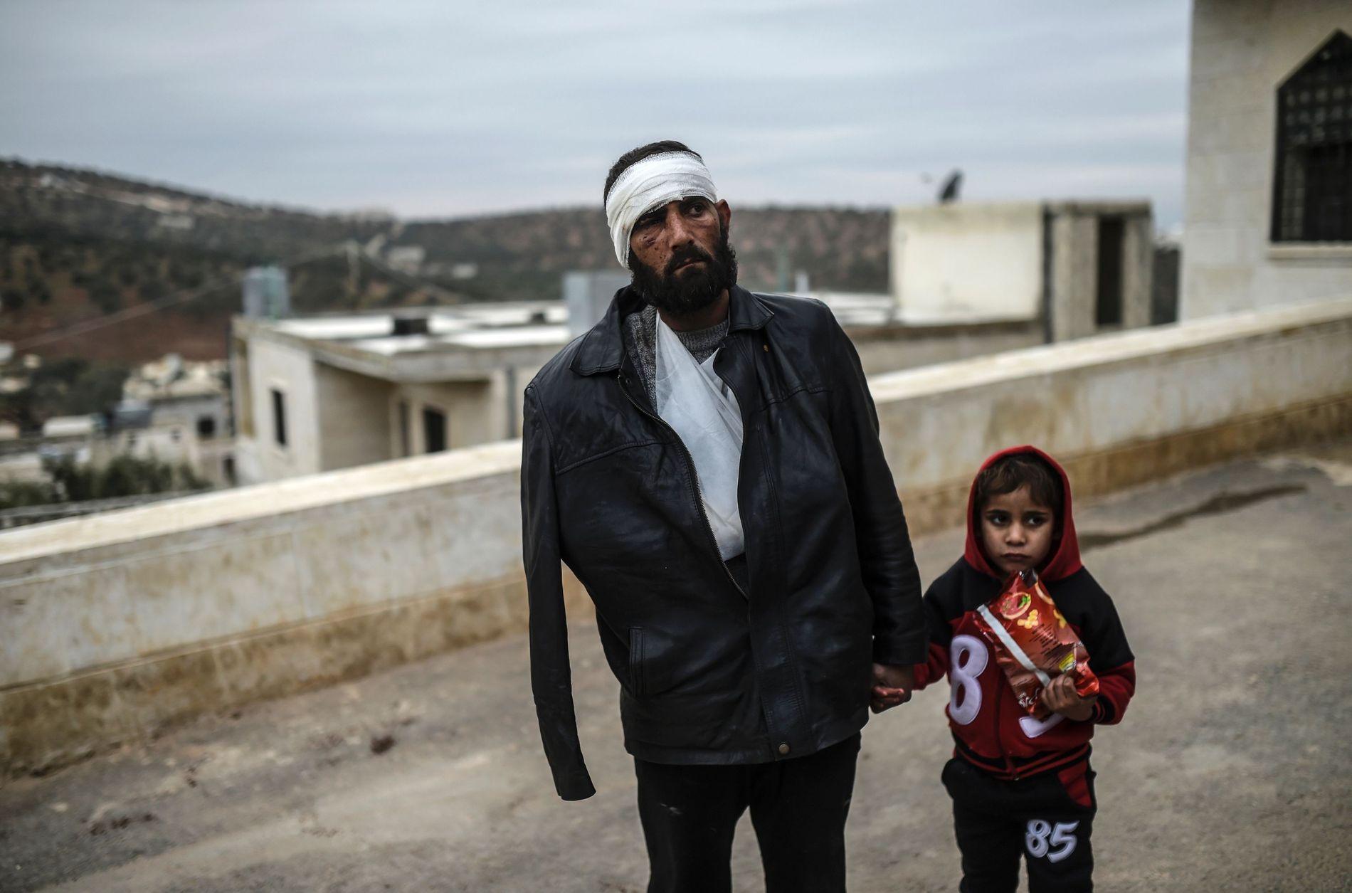 VENTER VED GRENSEN: En skadet mann og sønnen på den syriske siden av grenseovergangen Bab al-Hawa venter på å få legehjelp. Hardt skadete får midlertidig innreise til Tyrkia for medisinsk behandling.