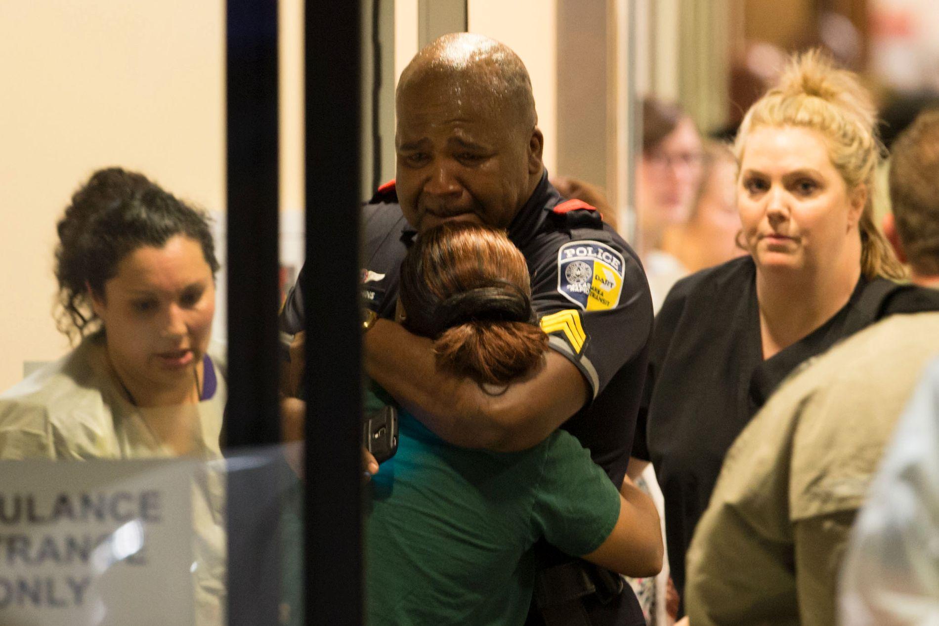 FORTVILET: En politibetjent får trøst på sykehuset etter det dødelige angrepet i Dallas.