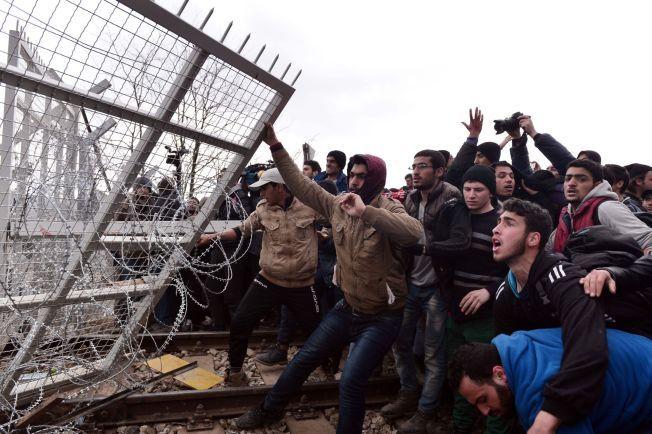RIVER GJERDET: En gruppe flyktninger klarer å dra ned sperringene som er dekket av piggtråd på grensen.