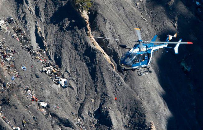 TOTALVRAK: Et fransk redningshelikopter flyer over restene etter Germanwings-flyet som styrtet i Alpene med 150 mennesker ombord.