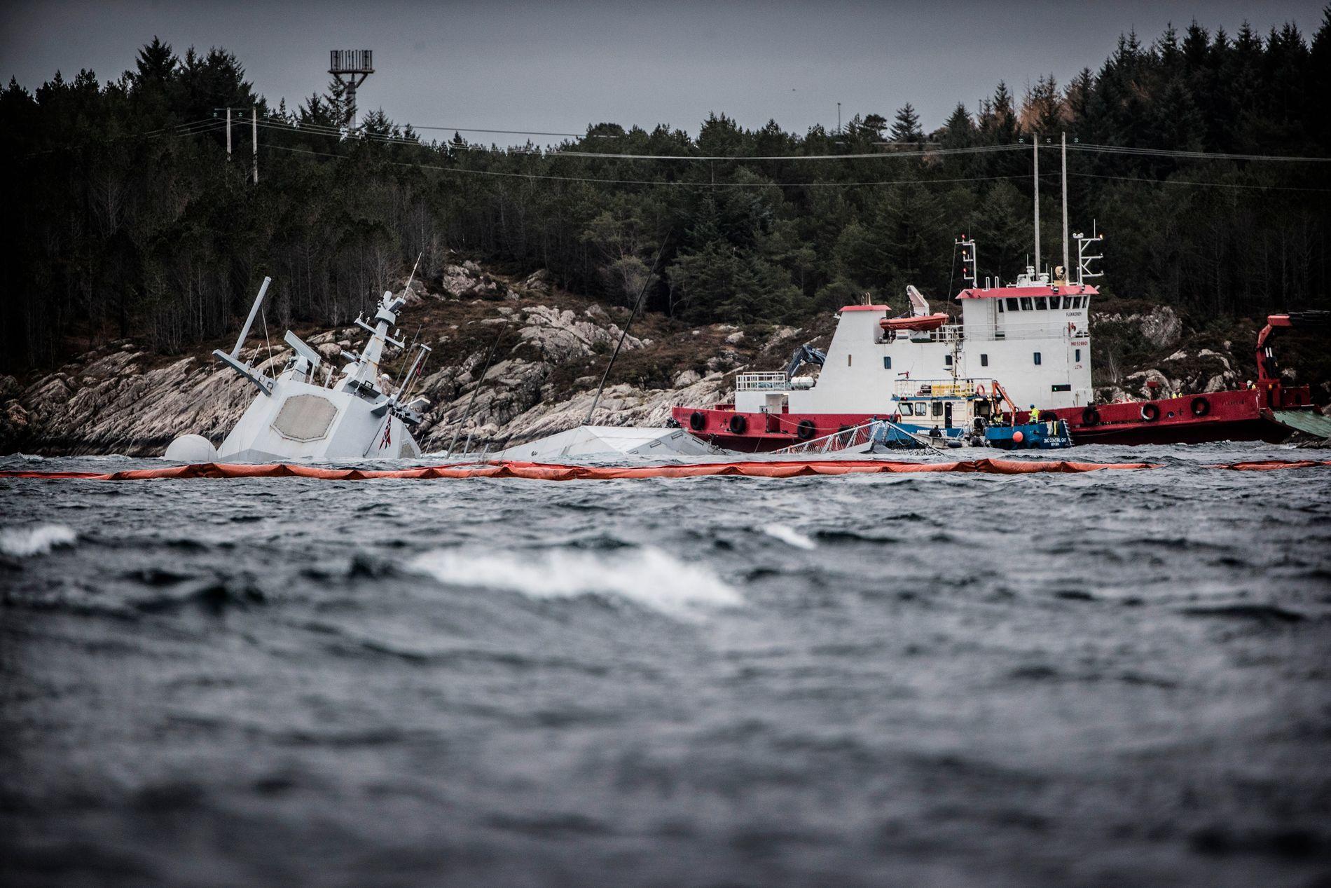 UNDER VANN: Den havarerte fregatten KNM Helge Ingstad (t.v) fotografert onsdag 14. november. Fregatten ligger på grunn nord for Stureterminalen i Hjeltefjorden utenfor Bergen.