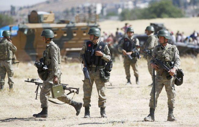 TRAPPER OPP: Tyrkiske soldater vokter grensen mellom den tyrkiske grensebyen Suruc og den kurdiske byen Kobane, 26. juni 2015. Tyrkia har lenge blitt kritisert for ikke å gjøre en god nok innsats i kampen mot Den islamske staten. Nå vil Tyrkia la den amerikanskledede koalisjonen mot IS bruke tyriske luftrom for å slå tilbake mot terrororganisasjonen.