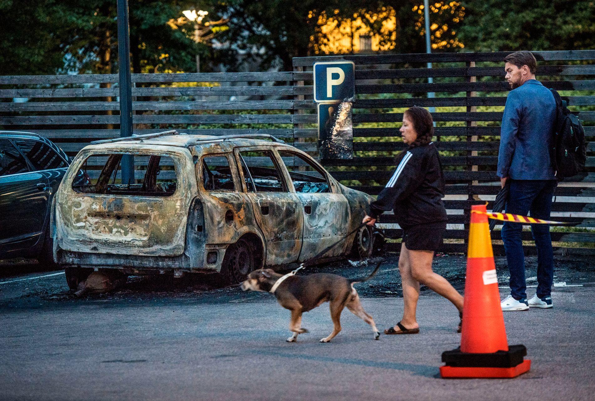 UTBRENTE BILER: På Frölunda torg i Gøteborg står det flere utbrente biler etter mandagens brannkaos. Tre unge menn så langt pågrepet, og politiet mistenker at ytterligere åtte til tolv personer står bak.