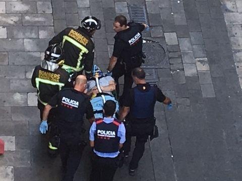 BÆRES BORT: Dette bildet, som viser en skadet person bli bært bort av helsepersonell. Bildet er tatt av Kim Pettersen, som leier leilighet rett ved gaten hvor terroren fant sted.