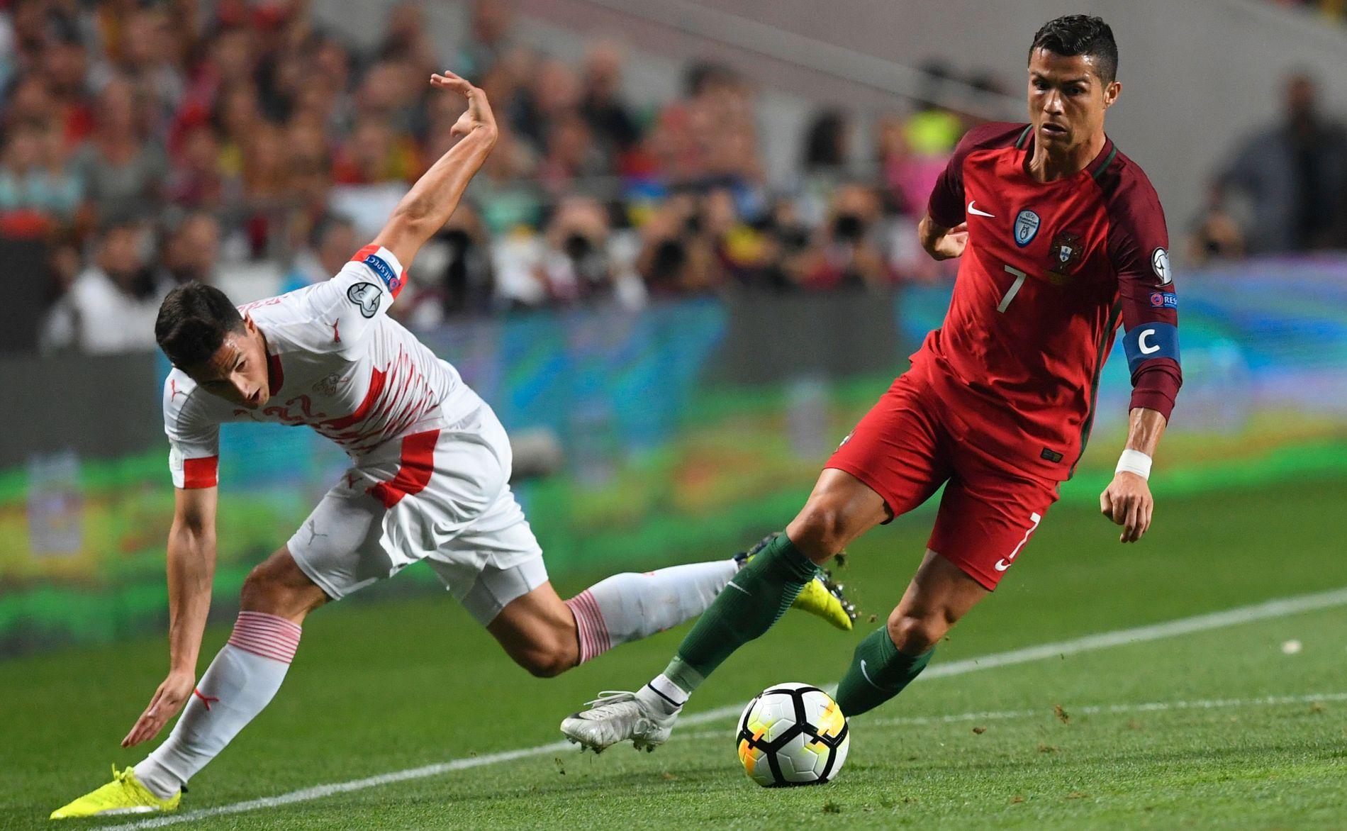OPS! Cristiano Ronaldo sender Sveits' forsvarsspiller Fabien Schar ut av banen i den avgjørende kvalik-kampen i Lisboa tirsdag.