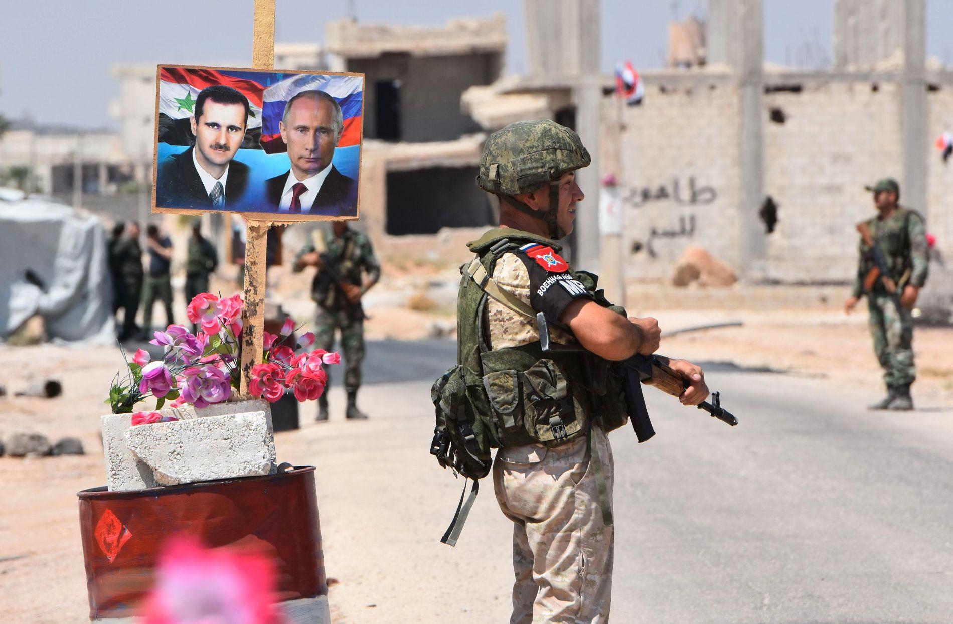 PARATE: Syriske og russiske soldater vokter en grensepassering i Abu al-Duhur i utkanten av Idlib-provinsen, med portretter av presidentene Assad og Putin ved sin side. Bildet er tatt 20. august.