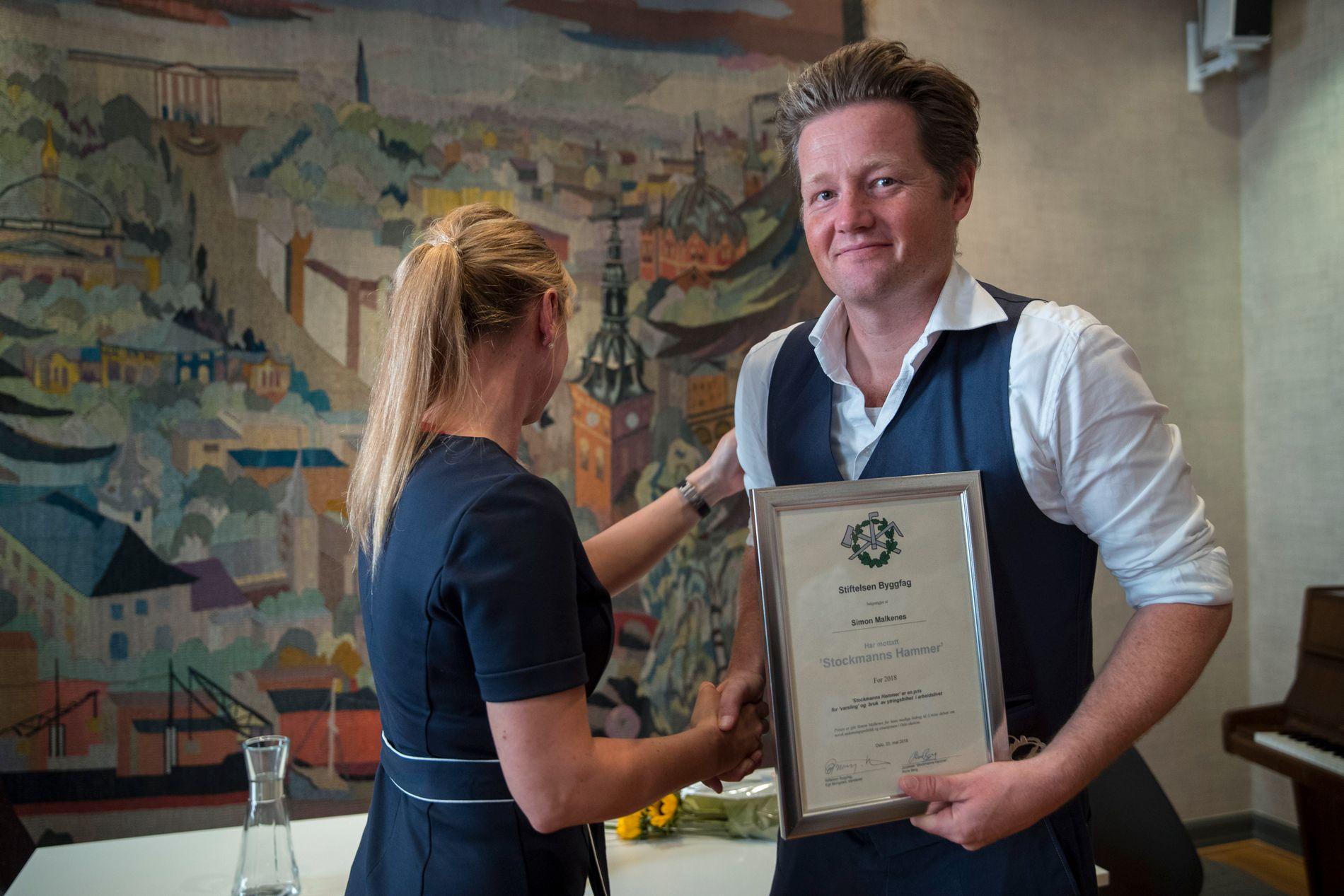 MOTTOK PRISER: Simon Malkenes har mottatt tre priser for sine ytringer om Osloskolen hittil i 2018. Her har han akkurat mottatt prisen Stockmanns Hammer fra Hilde Bergh i Oslo håndverker og industriforening 23. mai.