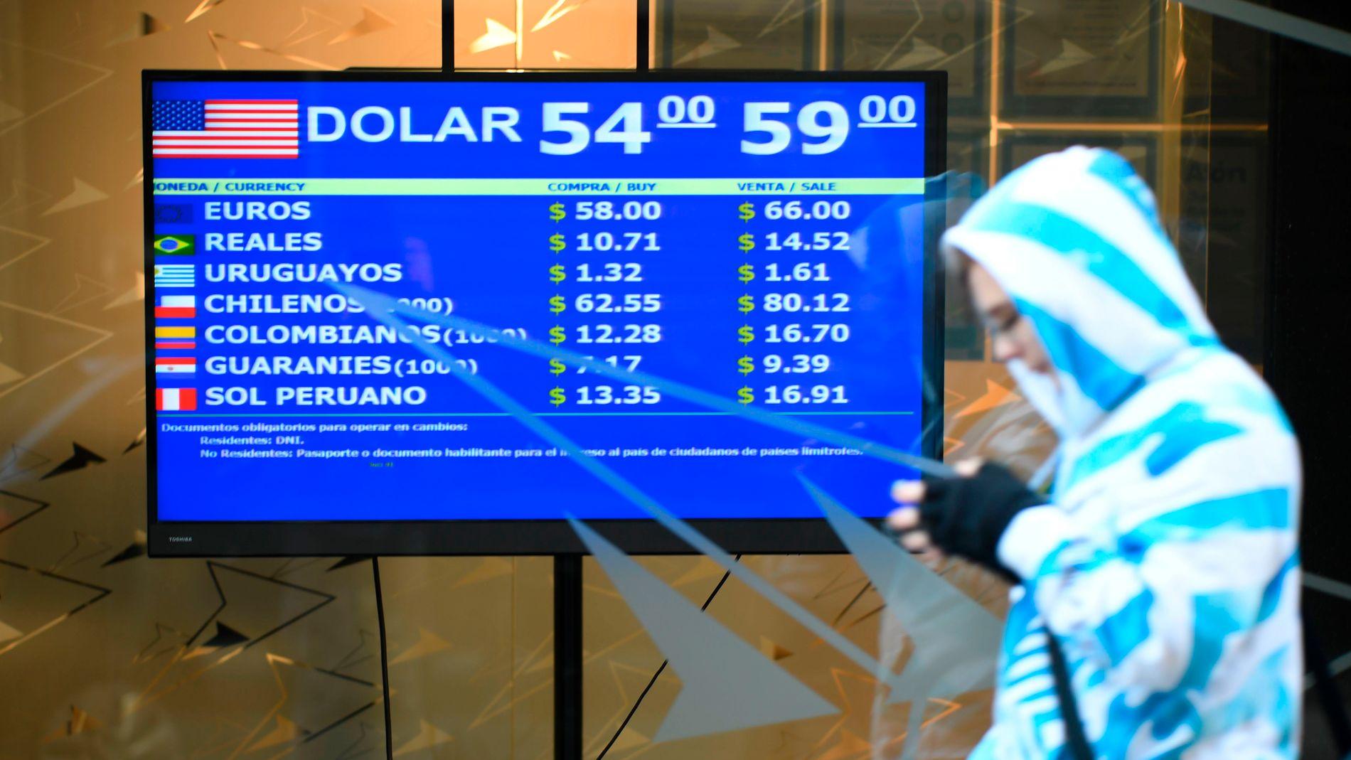 En skjerm i Buenos Aires viser valutakurser tirsdag 13. august. Den argentinske pesoen har svekket seg kraftig etter primærvalget søndag.