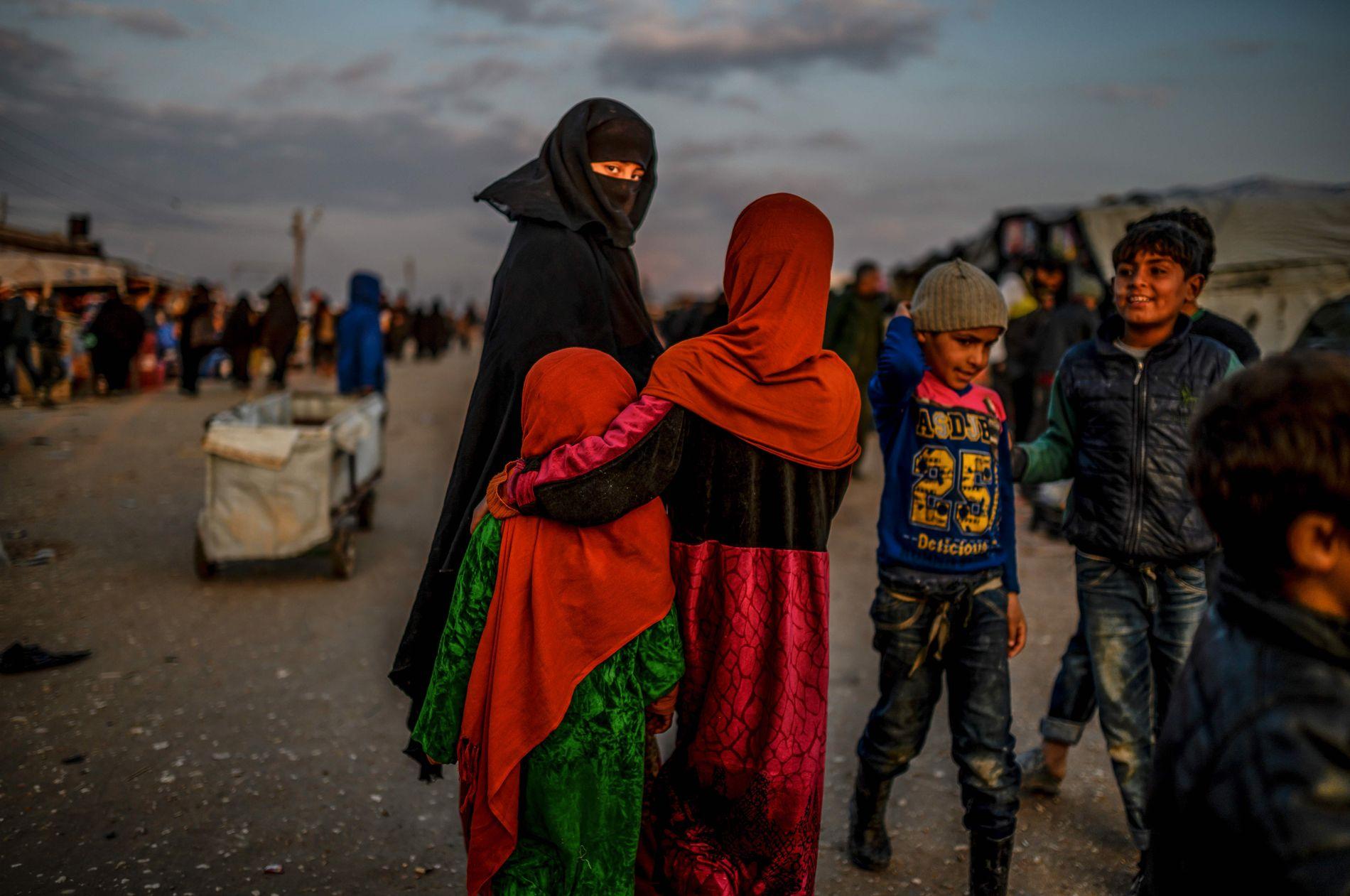 KVINNER OG BARN: En tildekket kvinne med to jenter ser mot kamera i samme leir som der de norske kvinnene sitter internert i Syria.