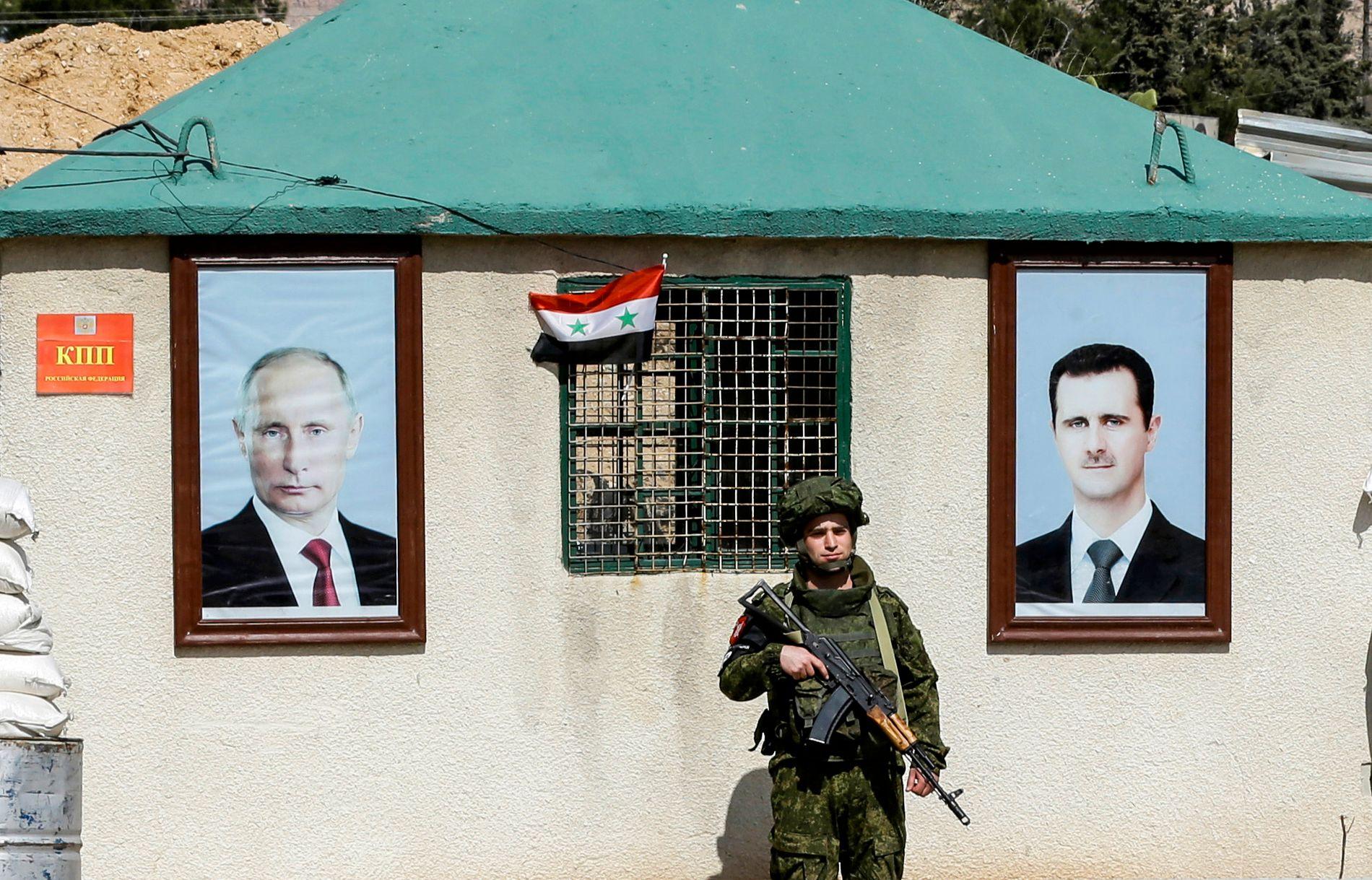 TRAPPER OPP: En russisk soldat står vakt like utenfor Øst-Ghouta mellom portrettene av Russlands president Vladimir Putin og Syrias president Bashar al-Assad.
