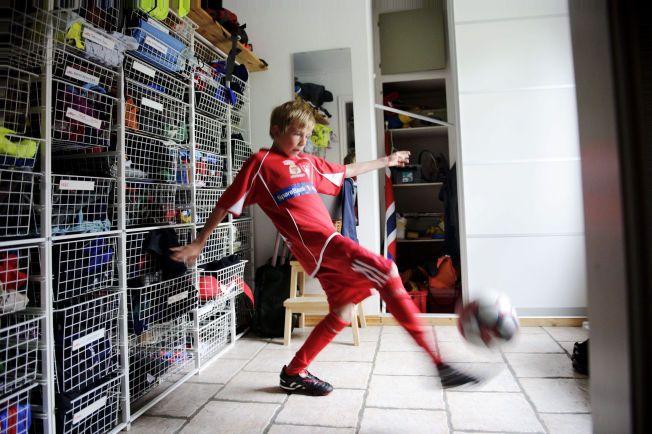 VARMER OPP: Erik Mårtensson (14) varmer opp til kamp for Vikersund IF hjemme i gangen foran kurvene med klær og  utstyr til fire søsken. Foreldrene betaler 1800 kroner i året til klubben for at Erik skal være med.