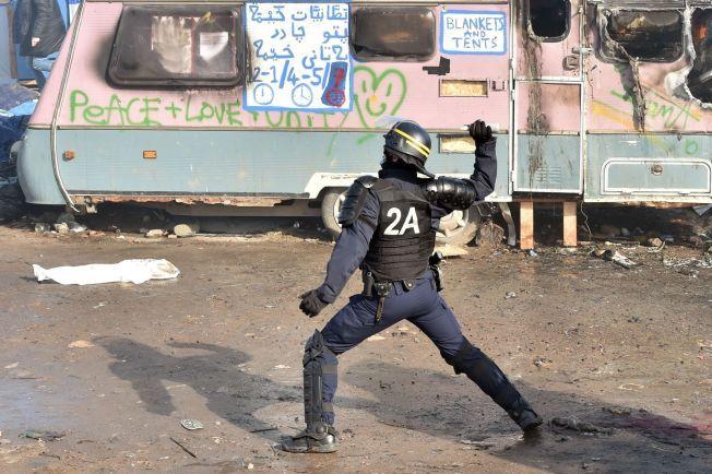 En fransk politimann er i ferd med å kaste tåregass, inne i «Jungelen» i den franske havnebyen Calais.