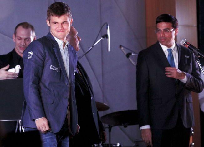 FORNØYD: Magnus Carlsen smiler etter å ha trukket svart i første parti i dagens VM-match i sjakk. Til høyre utfordreren Viswanathan Anand, som var verdensmester inntil Carlsens seier i India for ett år siden.