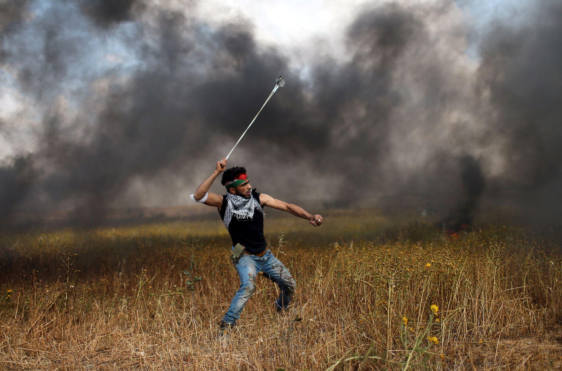 SINNE: En palestinsk mann kaster steiner mot israelske sikkerhetsstyrker under Gaza-demonstrasjonen forrige fredag.