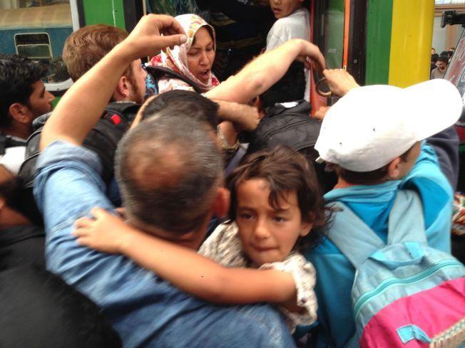 KJEMPER FOR PLASS: Foreldre med barn på armen kjemper seg ombord i tog de ikke vet hvor skal. Alle internasjonale avganger fra Keleti-stasjonen er innstilt.