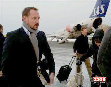 EVAKUERT: Her er kronprins Haakon avbildet utenfor flyet etter å ha blitt evakuert. Bak til høyre kan kronprinsesse Mette-Marit skimtes. Foto: Leserbilde til 2200