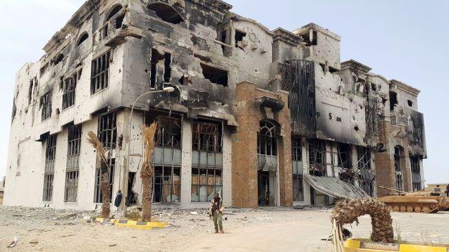 PÅ POST: En libysk soldat står foran ruinene av at kjøpesenter i Benghazi.