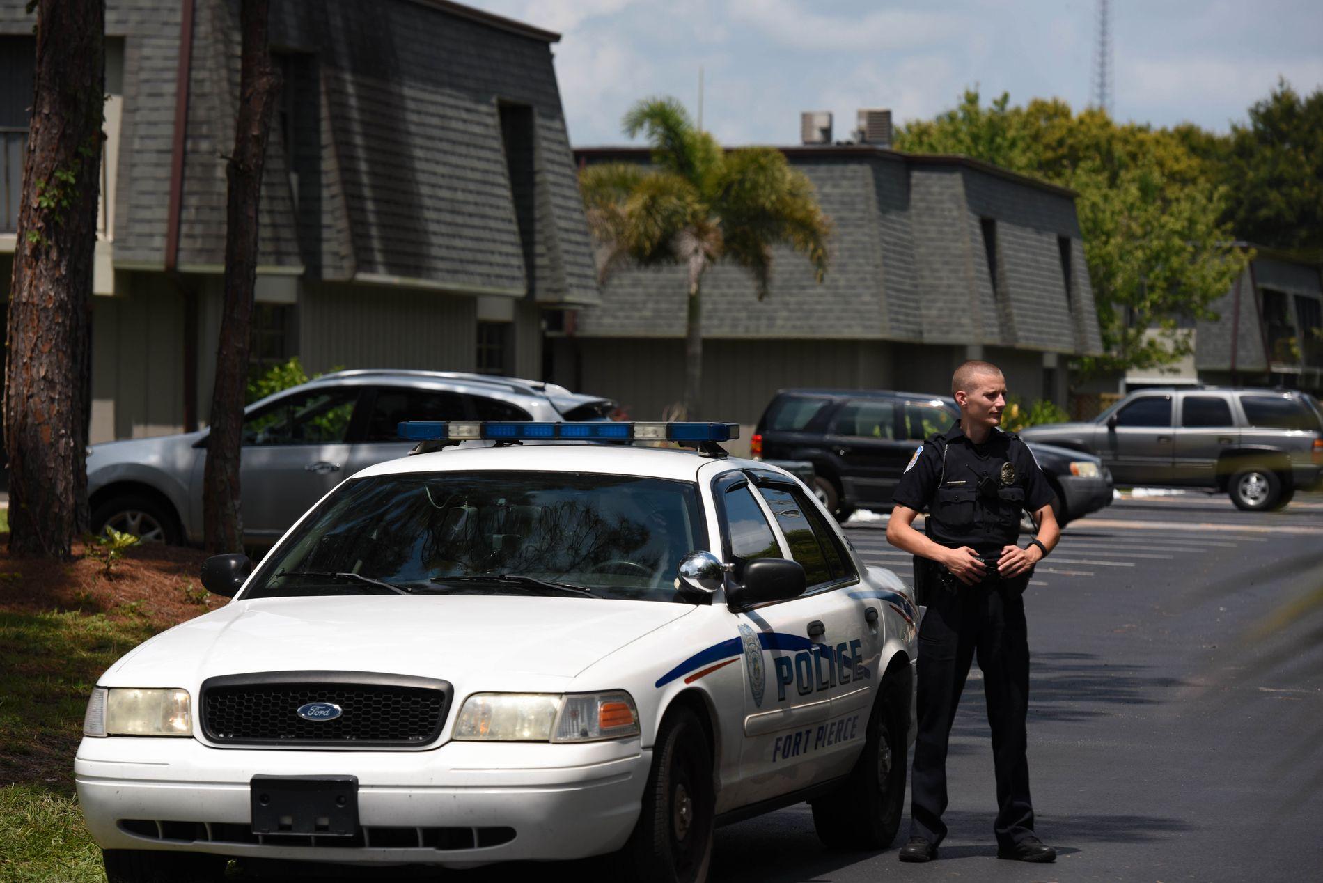 ETTERFORSKER: En politimann står utenfor leiligheteskomplekset Woodland i Fort Pierce i Orlando. De siste dagene har politi og sikkerhetsselskaper voktet området.