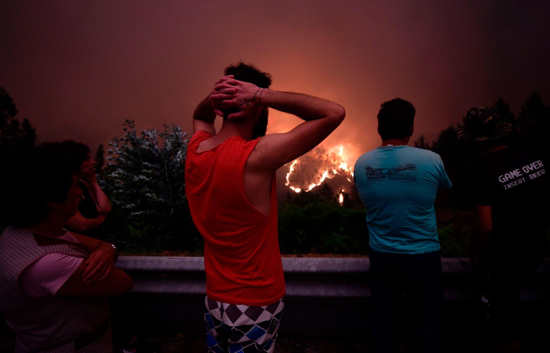 SER PÅ BRANNEN: Folk nær den portugisiske bygda Mega Fundeira ser på brannen som brøt ut lørdag.