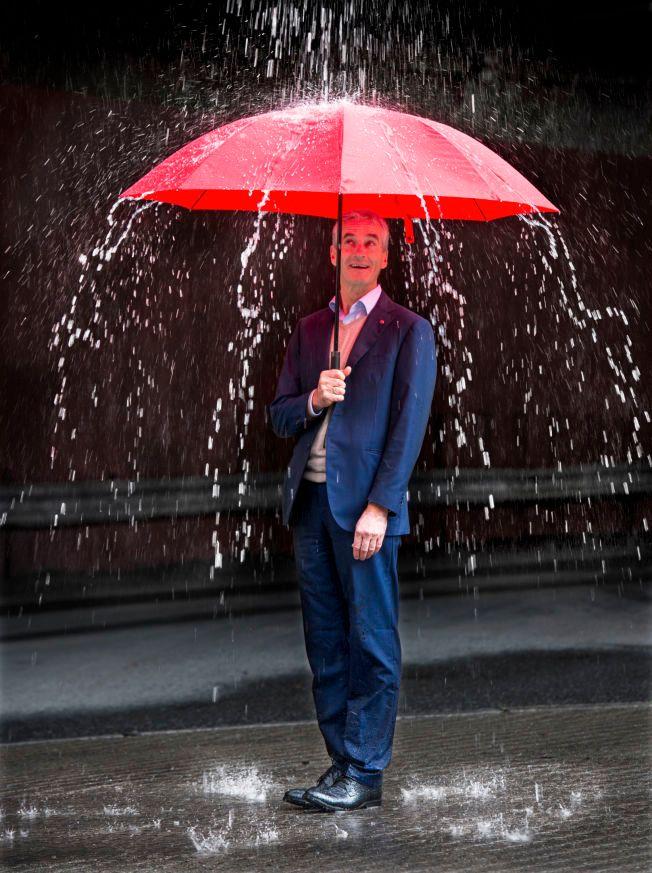 HELLER VANN: Mens Oslo brann- og redningsetat spyler vann mot Jonas Gahr Støre, står Ap-lederen med en rød paraply og holder seg såvidt tørr på benene.